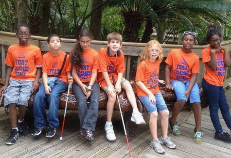 A group of 7 visually impaired students sitting on a long bench.